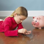 Girl laying on floor counting change by piggy bank