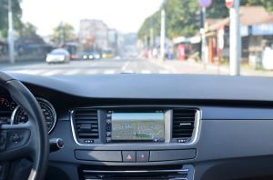 View of a car's dashboard, steering wheel, and street ahead.