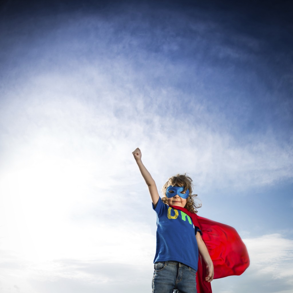 Boy wearing a cape and mask, dressed as a super hero, takes a superhero stance with an arm in the air.