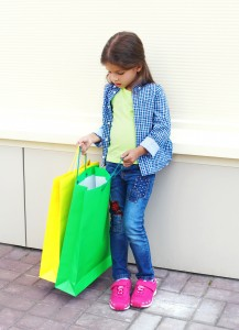 Beautiful little girl child with shopping colorful paper bags in