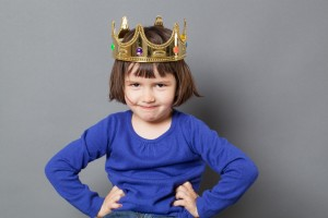 thrilled preschooler with confident attitude smiling with mollycoddled kid crown