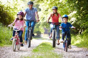 Family On Bicycle Ride In Countryside Smiling At Camera
