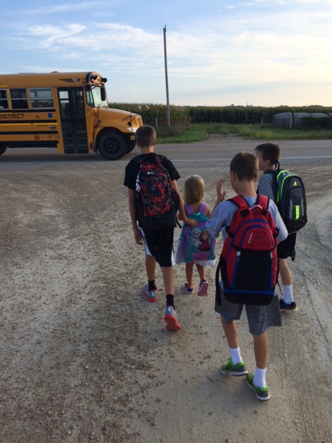 Four children are walking toward a yellow school bus.