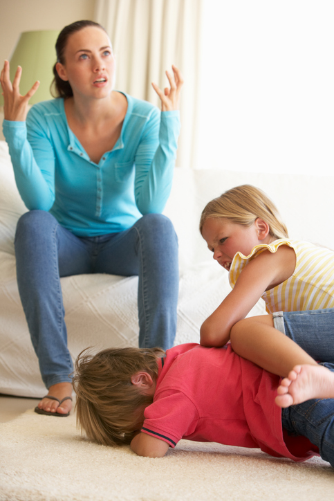 Two Children, a boy and a girl, fighting In Front Of their frustrated mother at home.
