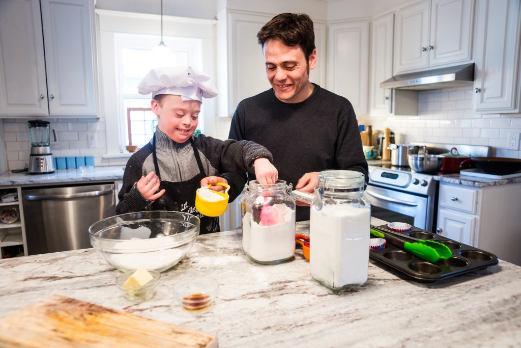 Boy wearing a chef's hat measures flour while baking with his father in the kitchen.
