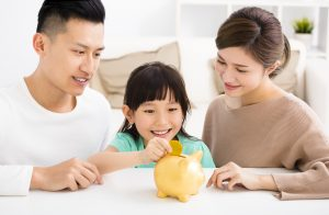 parent and daughter putting coins into piggy bank