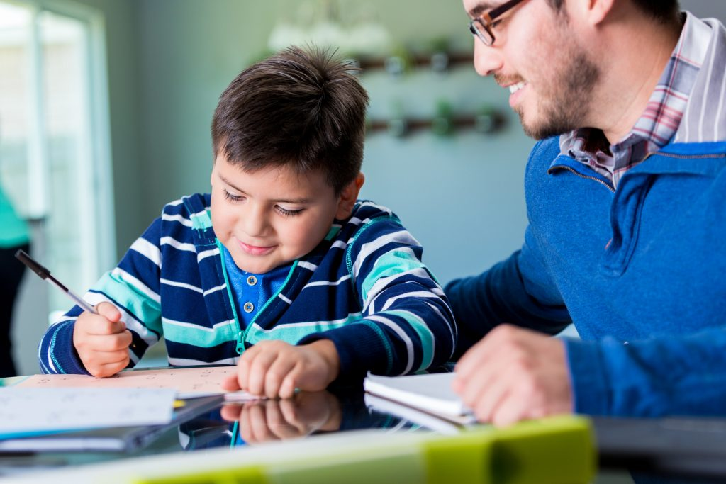Mid adult Hispanic father helps his elementary age son with his homeschool homework assignment. The little boy is writing on a pad as his father teaches him. They are sitting at the kitchen table.