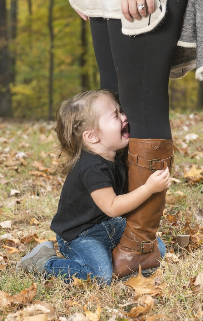 A small girl cries and clings too the feet of her mother