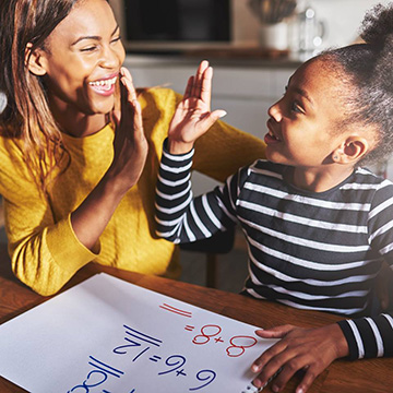 Mom is helping daughter with math homework, and they are high-fiving for a successful answer.