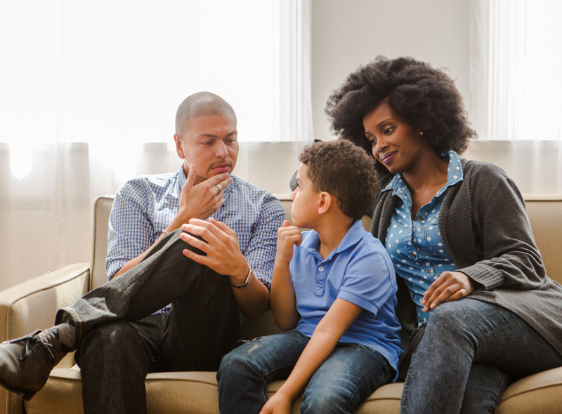 A father, mother, and son are sitting on a couch having a conversation.