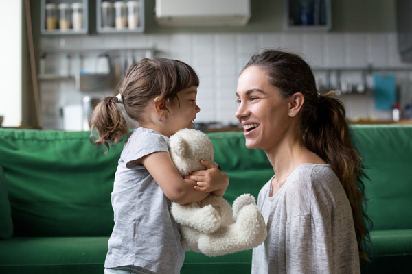A mother squats to her little daughter and smiles while her daughter holds a teddy bear.
