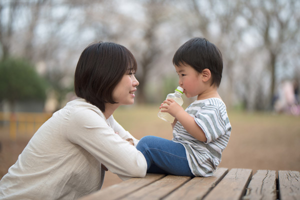 A mother is sitting on the seat of a picnic table while her son sits on the tabletop drinking out of a bottle.
