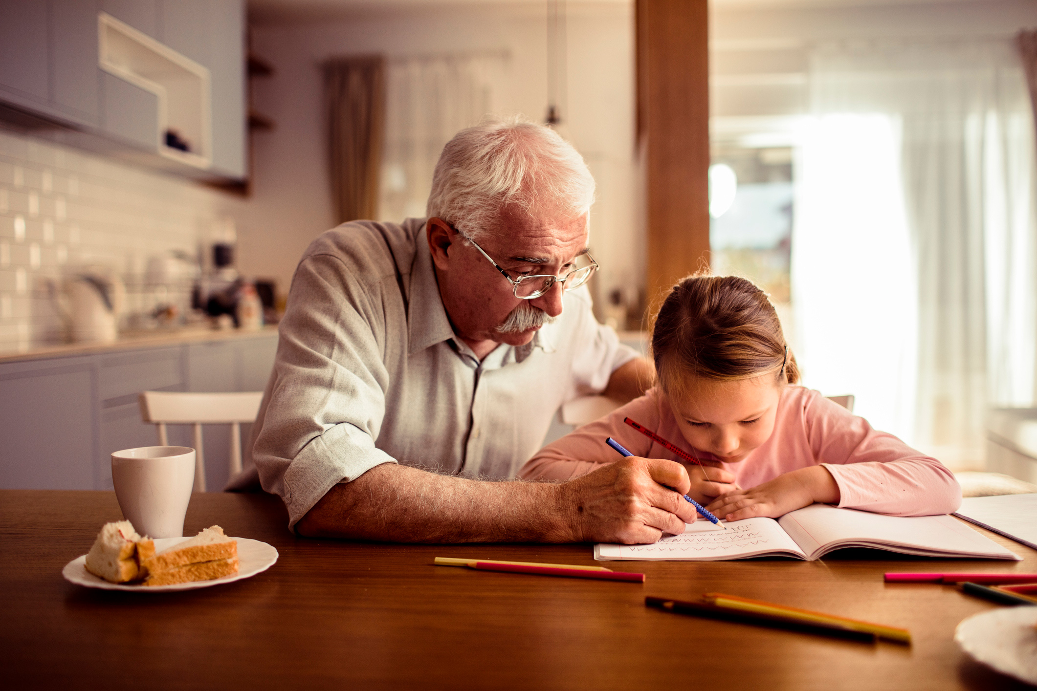 Grandfather and granddaughter are seated at the kitchen table while looking at homework. Grandfather is marking the workbook with a blue colored pencil while grandaughter observes.
