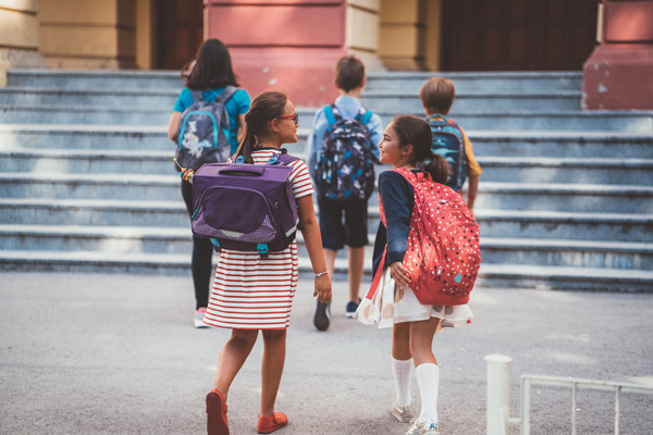 Five students walk towards the stairs in front of their school building, all wearing backpacks. The two girls in the back are chatting with each other.