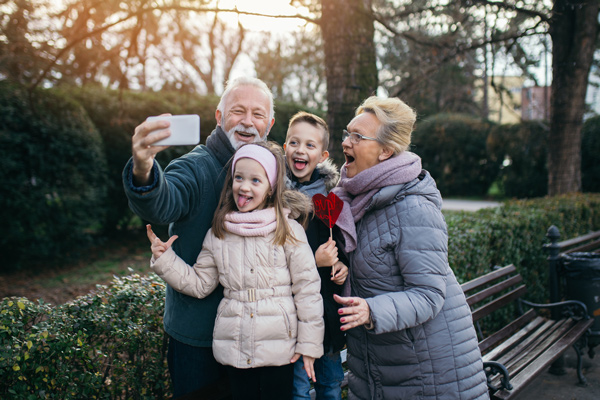 Grandfather and grandmother are taking a selfie with their grandson and granddaughter while out on a walk on a brisk day.