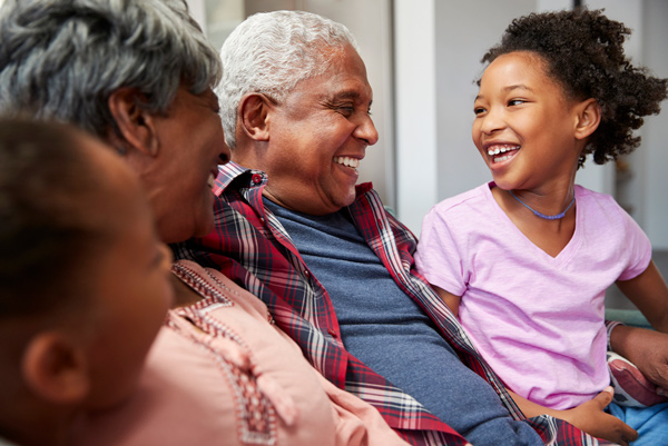 A close up image shows a grandmother and grandfather sitting on a couch with their two granddaughters, smiling and laughing with one another.