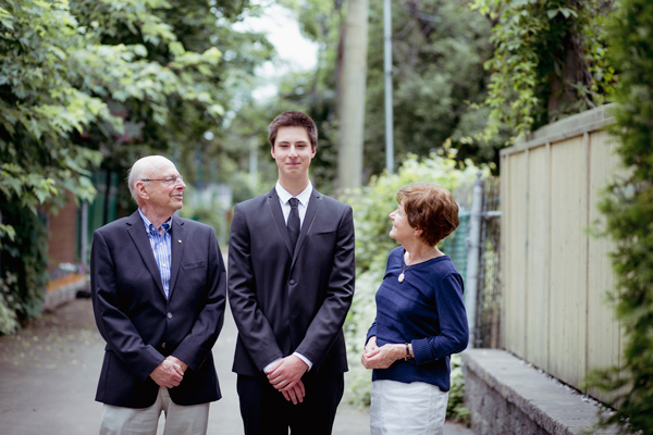 A tall teenager wearing a suit and tie stands between his grandfather and grandmother, who are looking up at him with pride.