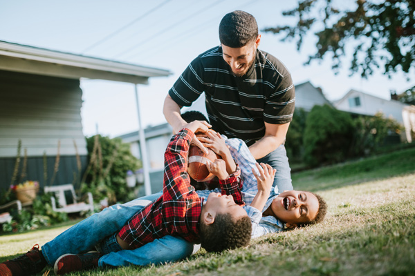 A father and his two sons happily wrestle a football from one another while they play in the yard.