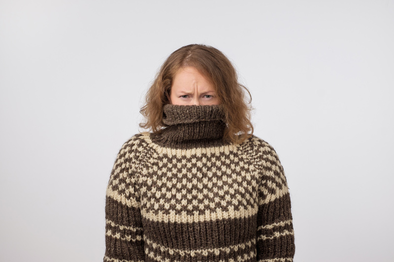 A woman stands in front of a white wall with a frustrated look in her eyes as she buries her chin, mouth, and nose into the neck of her sweater.