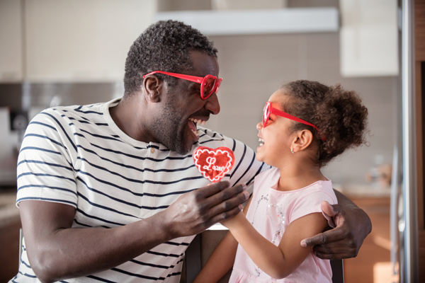 A father and daughter look at each other joyfully, both wearing red heart sunglasses and holding a heart-shaped sucker together.