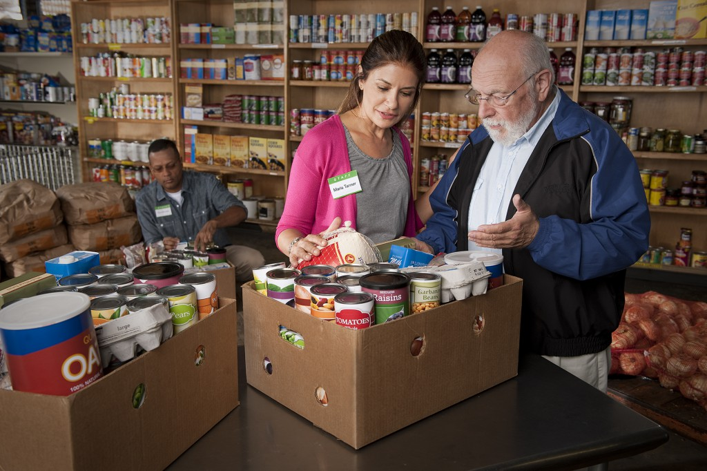 woman helping man at  food pantry