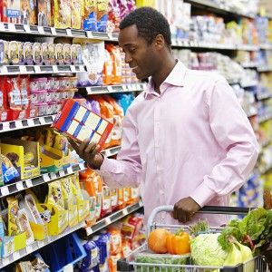 man reading food label grocery store