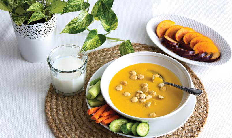 Bowl of soup with vegetables, fruit, and milk